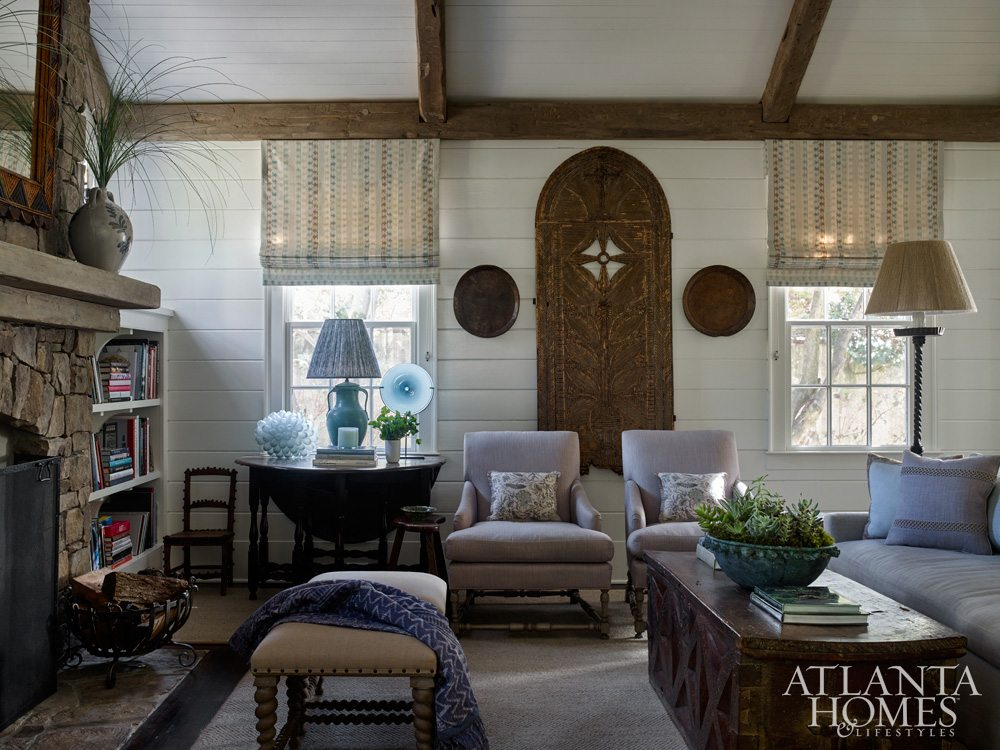 A chic throw and complimenting pillows add a cozy ambiance to this space, image via Atlanta Homes & Lifestyles.