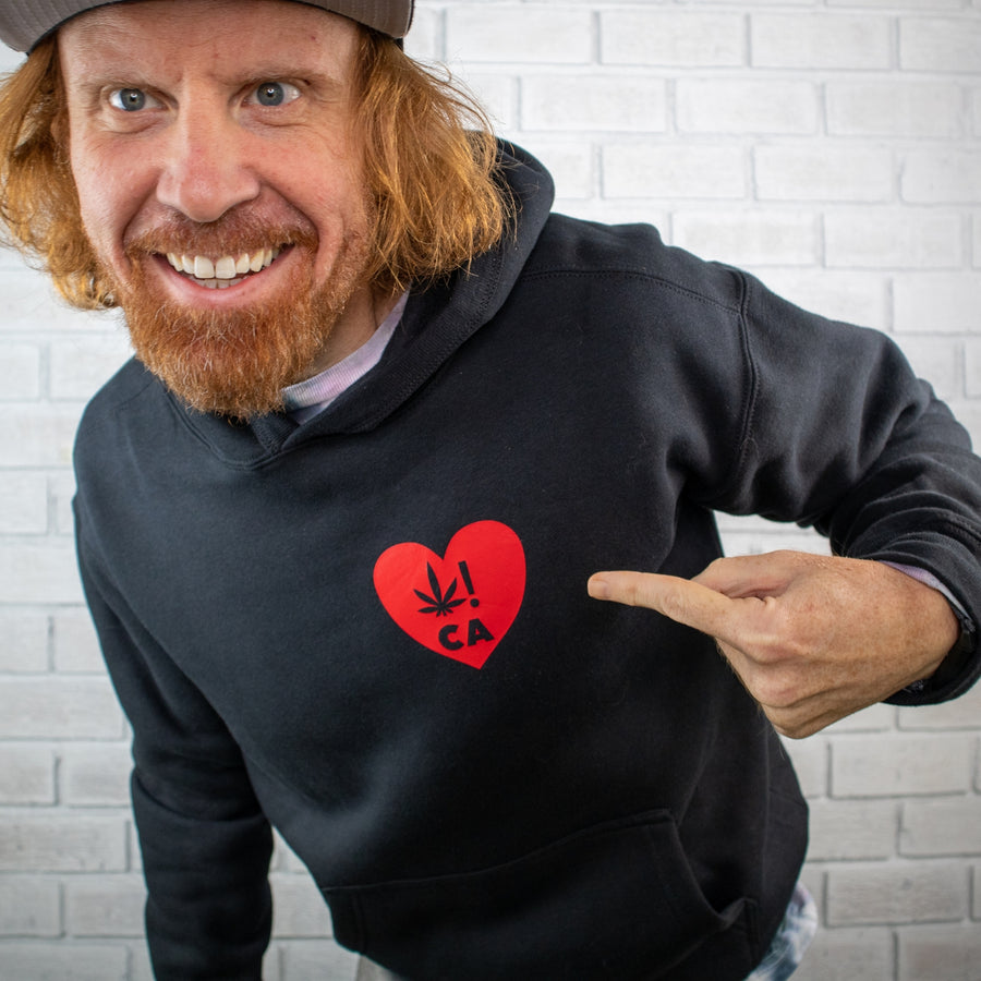 Man with red hair wearing a black hoodie sweatshirt against an all white brick wall. The black sweatshirt is decorated with a red heart logo on the left chest. The man is pointing at the red heat logo.