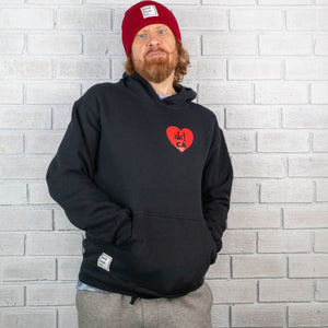 Man with red hair wearing a black hoodie sweatshirt leans against an all white brick wall. The black sweatshirt is decorated with a red heart logo on the left chest.