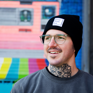 Smiling man with large neck tattoo wearing a good kush company beanie in The Black colorway.