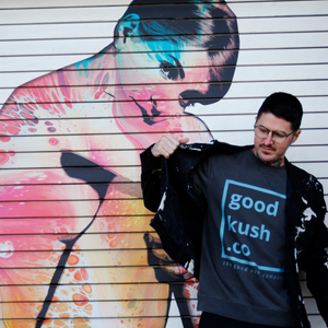Man opening his jacket to reveal a good kush company Big Blunt Logo sweatshirt in Buzz City teal color. The wall behind the man is a woman in pink and blue colors.