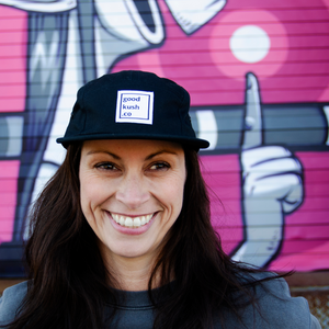Black five-panel hat with the good kush company logo being worn by a smiling woman.  The background is a hot pick wall moral. The woman has been smoking cannabis and is very happy.