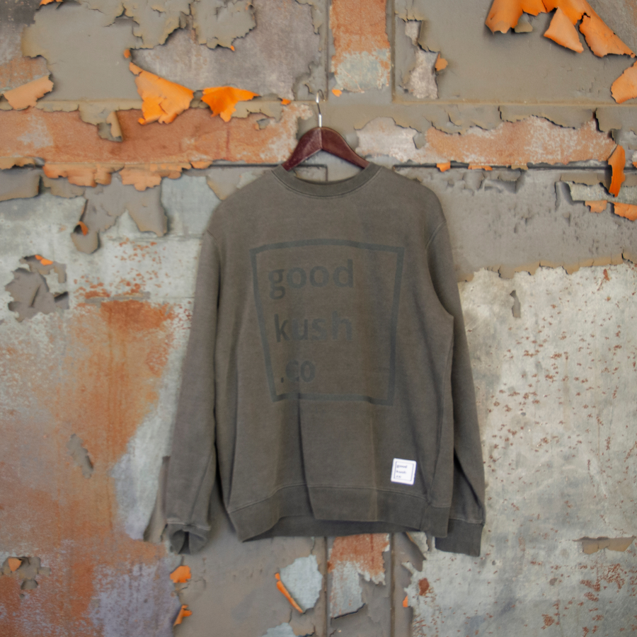 Faded black sweatshirt on a hanger. The black logo for the good kush company is barely visible on the sweatshirt.  The wall behind the Big Blunt sweatshirt is metal and rusty.