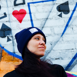 Woman looking away wearing a Blue Dream beanie. A two of diamonds playing card is spray painted on the wall behind her.