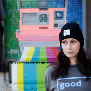 Woman looking relaxed wearing a good kush company sweatshirt and The Black beanie cap standing in front of a colorfully spray painted door.  The woman smokes marijuana.