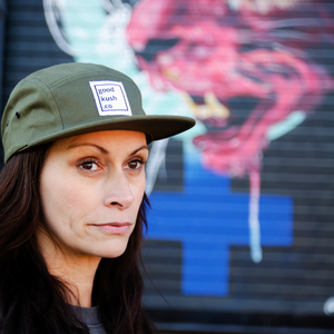 Woman with long black hair wearing an olive green colored cap. The cap displays the good kush company logo. A mural of a red lion is in the background.