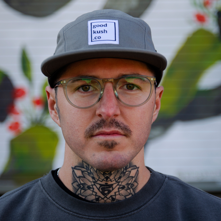 Man with glasses and large neck tattoo wearing a light grey cotton hat. The good kush company logo is centered on the crown of the hat.