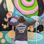 "Redheaded man facing a brightly colored wall wearing a long sleeved dark grey t-shirt. The phrase ""Anti-Corporate Cannabis Tokers Club"" is printed on the back of the shirt with white lettering."