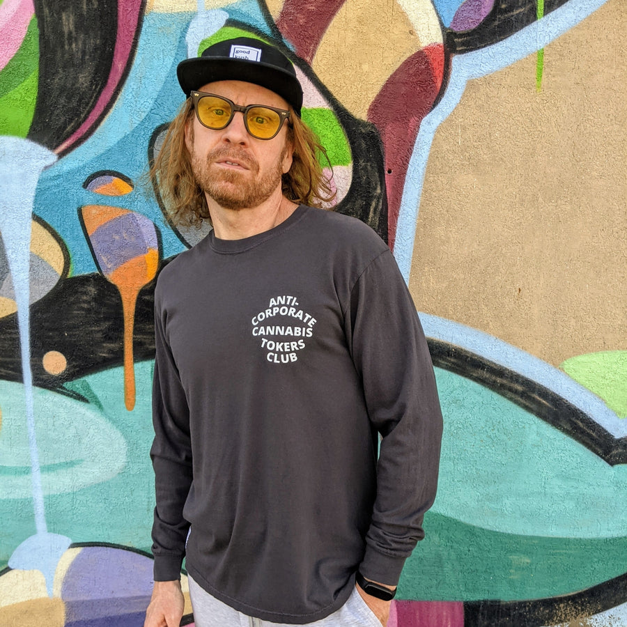 "Redheaded man leaning against a wall in long sleeved dark grey t-shirt. The phrase ""Anti-Corporate Cannabis Tokers Club"" is printed on the shirt's left breast with white lettering."
