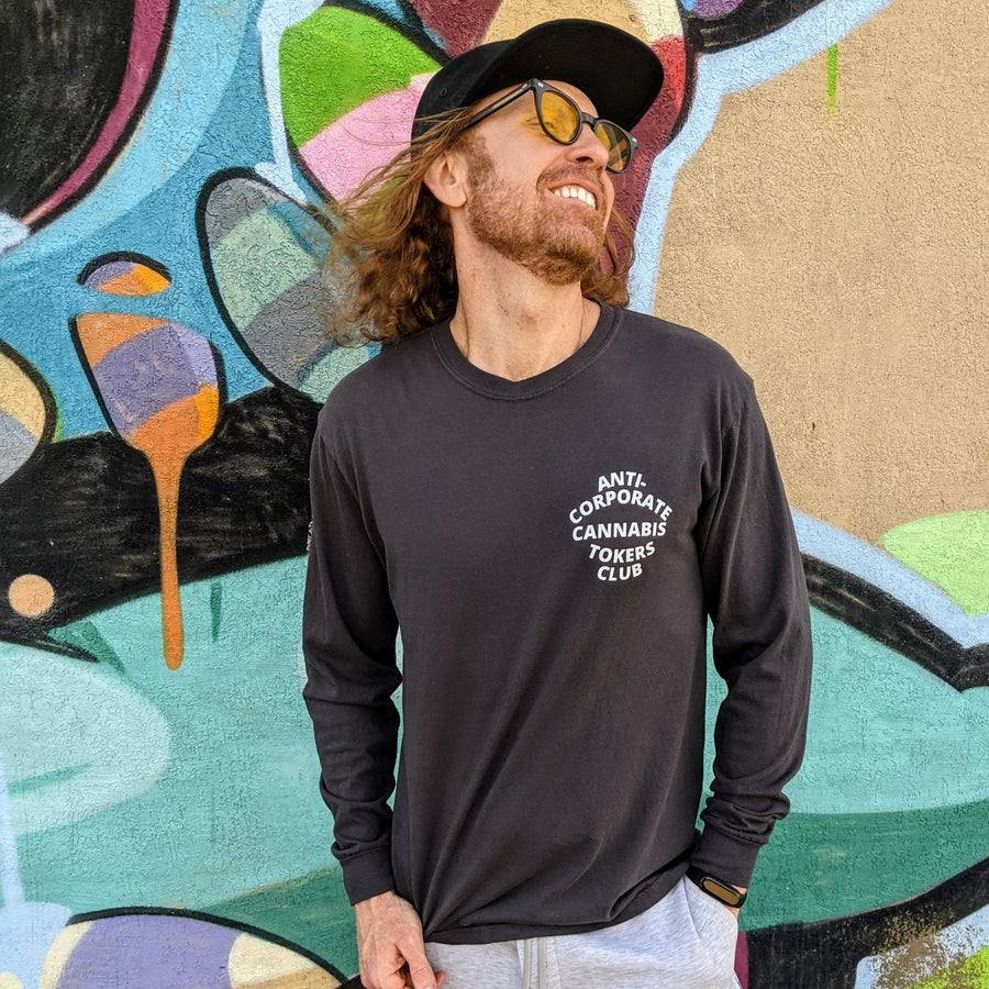 "A smiling redheaded man leaning against a wall in long sleeved dark grey t-shirt. The phrase ""Anti-Corporate Cannabis Tokers Club"" is printed on the shirt's left breast with white lettering."