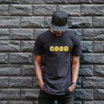A Black man leans against a black wall. He is wearing a black tshirt with the word GOOD in yellow across his chest.