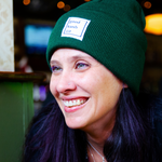 Laughing woman leaning against a counter. She is wearing a Lil' Blunt Beanie in the color Green Queen.