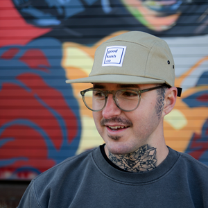 Man with glasses and neck tattoo wearing the good kush company hat in the alternative khaki (tan) colorway.  The man clearly smokes marijuana.
