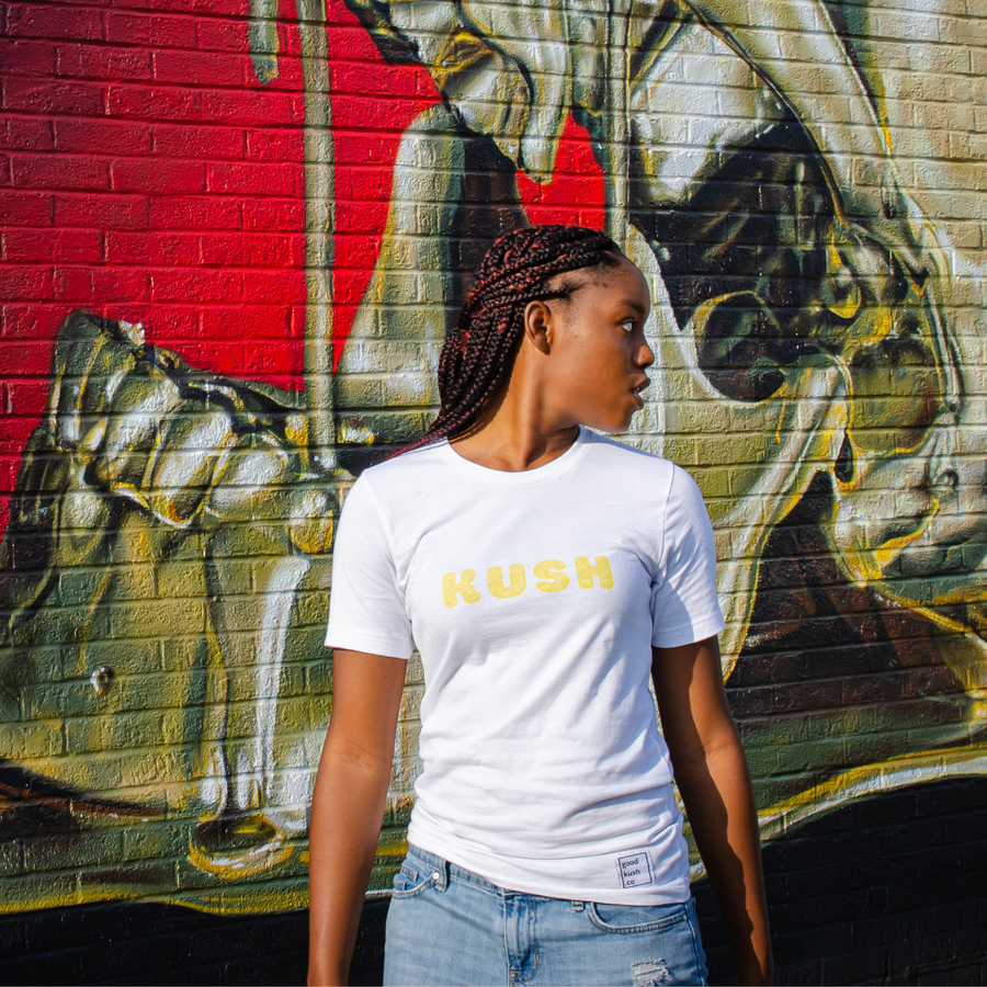 Young Black woman is looking off in the distance. She wears a white t-shirt with the word KUSH across her chest. Her background is a red and gold wall mural.
