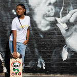 Young woman holding skateboard leaning against a wall that is painted with an iconic image of Bob Marley smoking a joint. The young lady is wearing a white super lemon haze kush t-shirt.