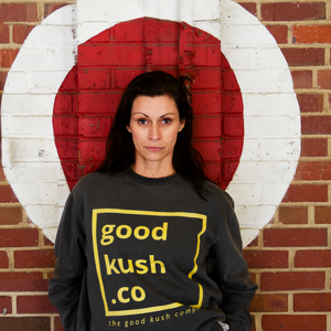 Woman standing in front on a painted bullseye on a wall.  She is wearing a dark grey sweatshirt with the good kush company logo in a gold colorwar.