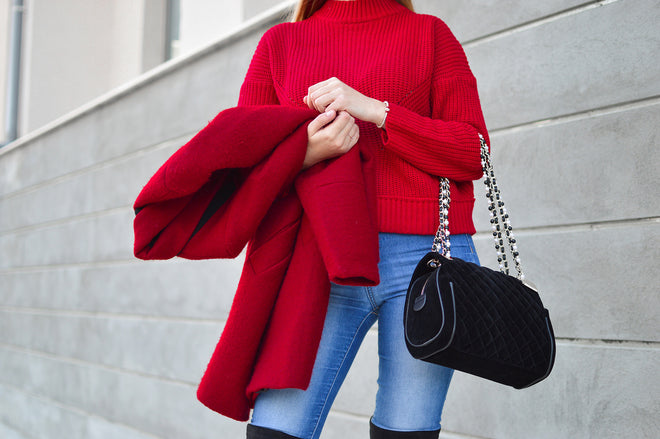 Girl in Red jumper, with red coat, and black handbag, wearing jeans,Eezy fabric comb removes fuzz balls, hair balls, bobbles, dog and cat hair, lint, dust, from your Knitwear and upholstered couches, dining chairs, upholstered bedheads, rugs and carpets.