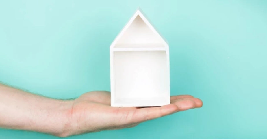 Hand holding a crafted white little house