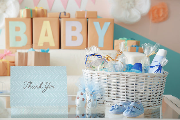 Baby shower gifts and decorations with baby blue thank you card and gift basket on the table