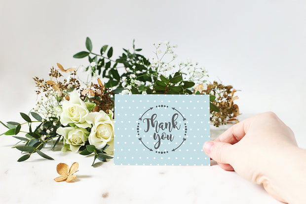 Baby Blue Polka Dot Thank You Note with somebody holding the card in front of a bouquet of flowers
