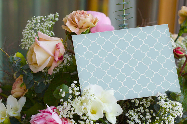 Baby blue patterned get well soon or sympathy card sitting in a bouquet of flowers