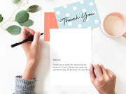 Person writing a thank you note with leaves, milk, and thank you cards above their hands
