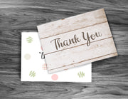 Distressed wood thank you note laying on top of a polka dot thank you card on black table