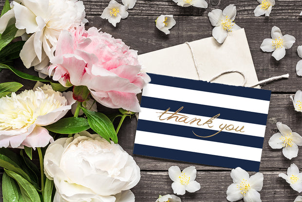 Foiled with Blue Stripes Thank You Card and white envelope laying on a table surrounded by flowers