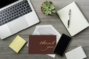 Foiled Maroon Thank You Card and white envelope laying on an office desk surrounded by office supplies