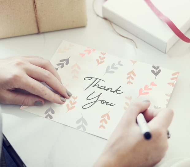 Woman's hands writing on a pastel falling leaves thank you note surrounded by presents