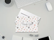 Pastel Floral Thank You Card and white envelope laying on an office desk surrounded by office supplies