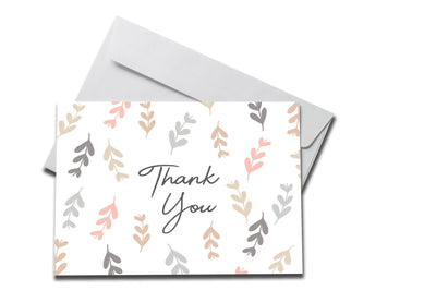 Pastel Falling Leaves Thank You Card laying on a white envelope