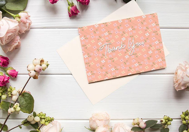 Peach Floral Thank You Note laying on envelope surrounded by roses