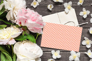 Peach Polka Dot Get Well Soon Card and envelope laying on a wood table surrounded by roses and flowers