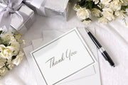 Foiled Silver Thank You Card and envelope laying on a table surrounded by wedding presents