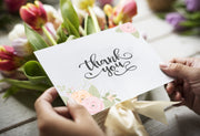 Woman holding a rose petals thank you card above a bouquet of tulips