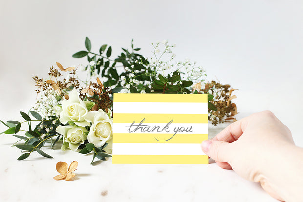 Yellow Striped Thank You Note with someone holding the card and a flower bouquet in the background