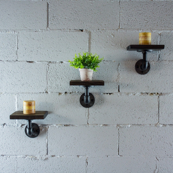 Three Paulownia wood rustic industrial chic decorative shelves with dark brown stained wood, candles and a house plant.