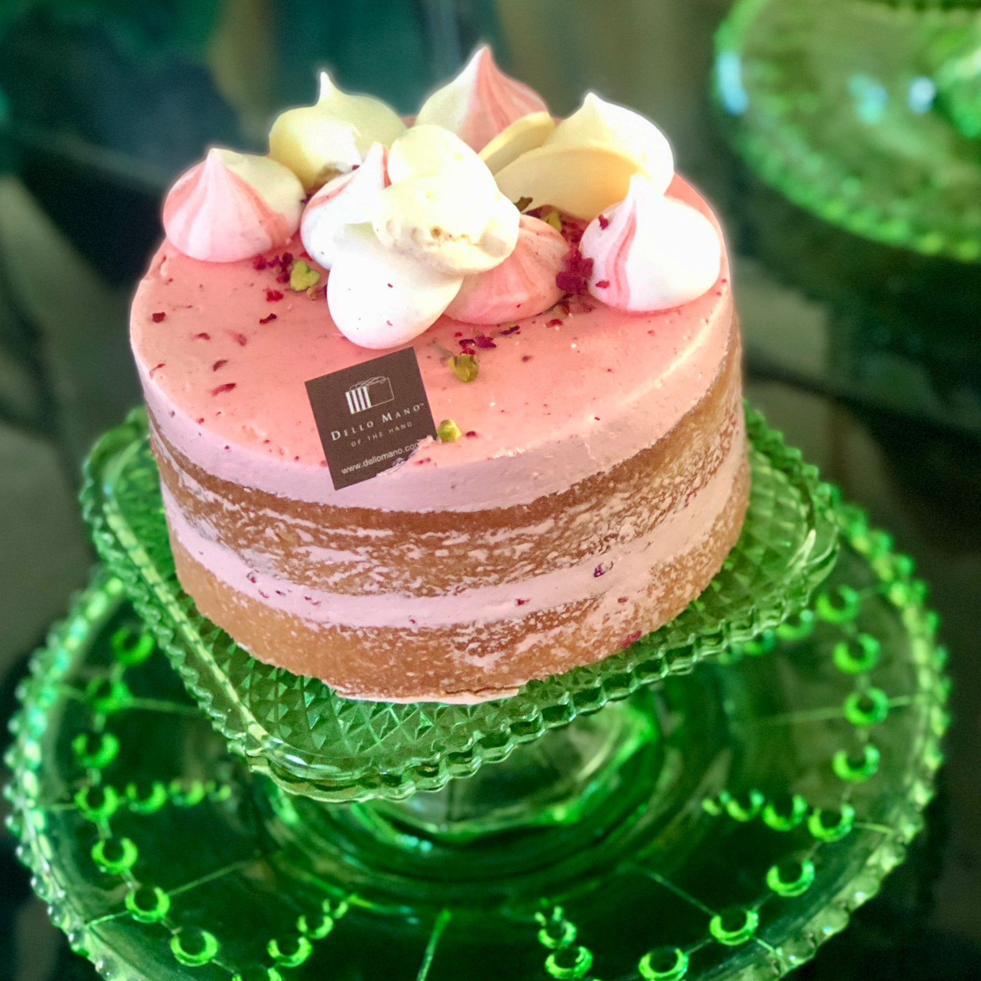 A pink cake on a green stand with Dello Mano Label