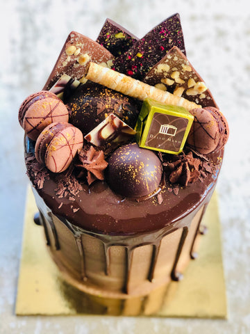 A tall chocolate drip cake showing chocolate ganache dripping and on top lots of chocolate decorations including truffles, chocolate domes, macrons and a gold foiled brownie