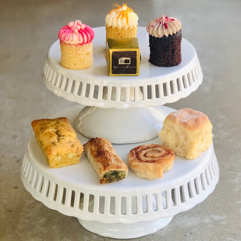A white two tiered cake stand with High Tea sweet and savoury treats