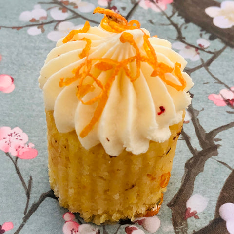 A high tea mini orange cake with frosting and orange zest on a Japanese blossom background