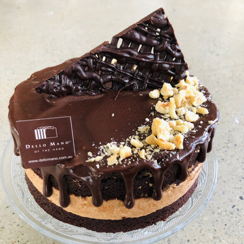 Hazelnut Mousse Cake showing layers of cake and mousse with kibbled hazelnuts and chocolate decoration on top.