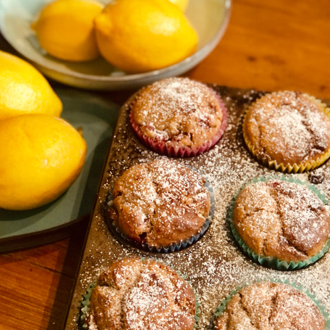 Strawberry Muffins in a baking tray with icing sugar sprinkles and lemon in the background