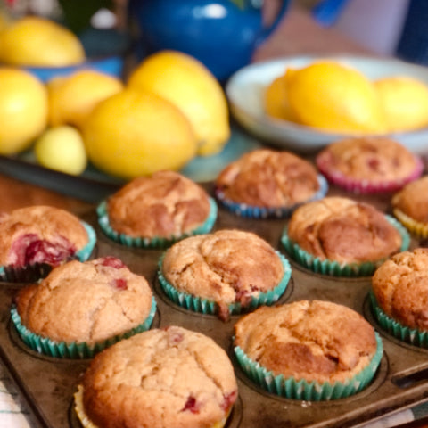 Strawberry Muffins in cases on baking tray with lemons in the background