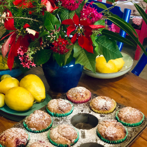 Strawberry muffins on timber table with lemons and a blue jug with red flowers