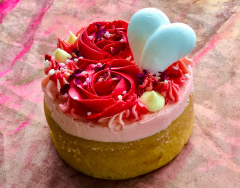 a pink cake with red valentines day roses made from buttercream frosting