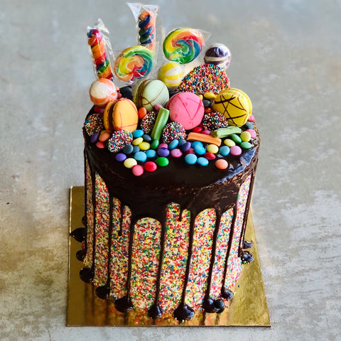 A chocolate drip birthday cake with sprinkles and lolly decorations