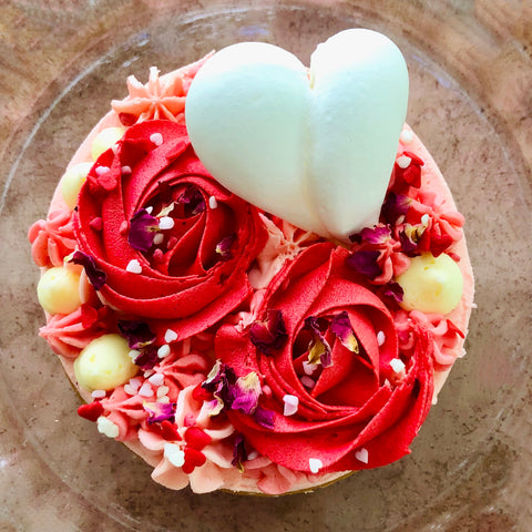the top of a red rose valentine cake finished with meringue heart