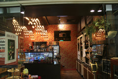 The store interior with cakes, brownies, red wallpaper & sign saying Dello Mano